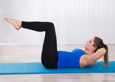 Woman Exercising In Yoga Class